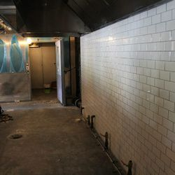 Partial view of the kitchen with tiled walls and large walk-in cooler.