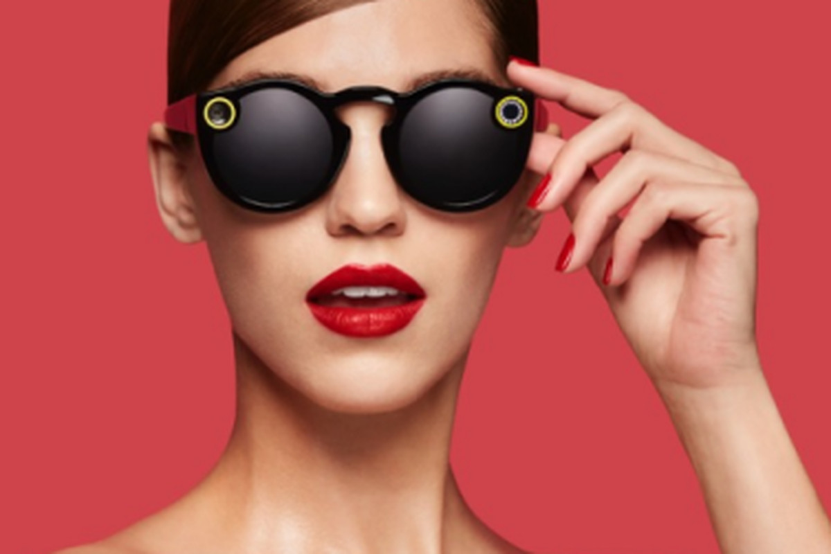 A model wearing Snap glasses against a pink background