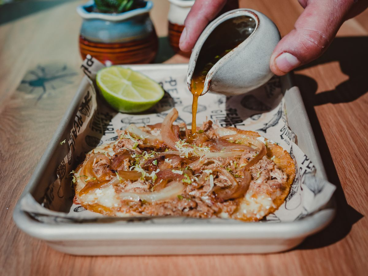 A hand pours a thin brown broth from a small white sauce cup onto a meaty taco that sits on a silver tray. The tray is on a table, with two small succulent plants in the background.