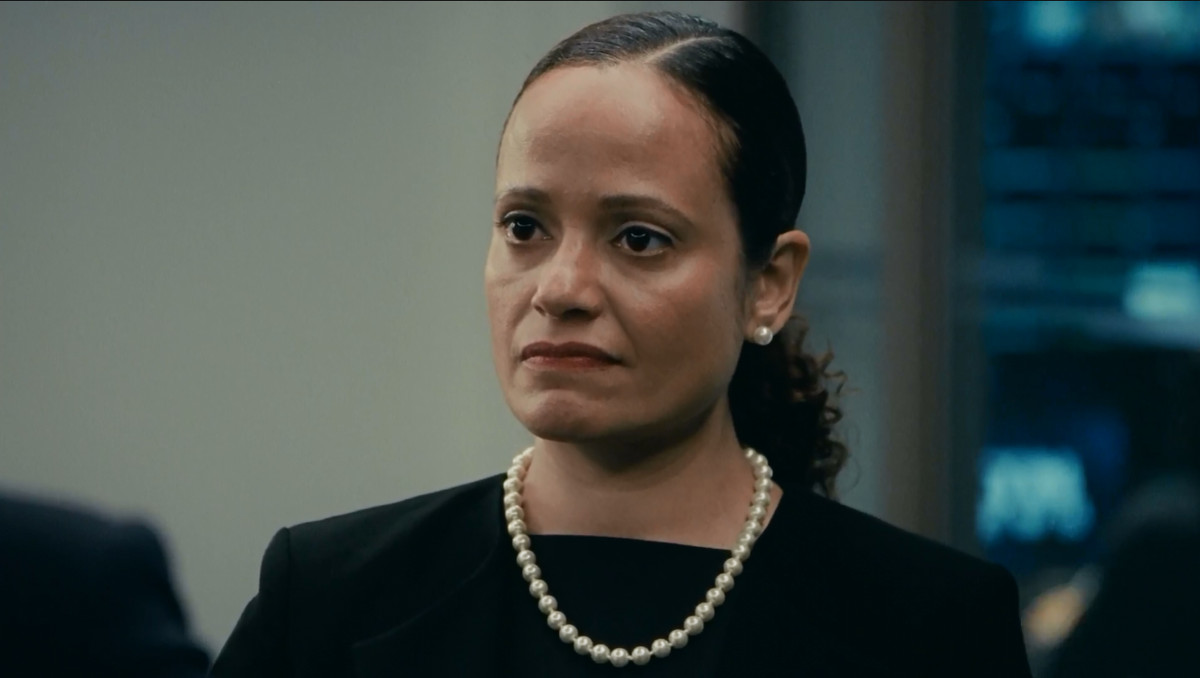 Judy Reyes in 'Succession,' looking angry and wearing a pearl necklace and earrings