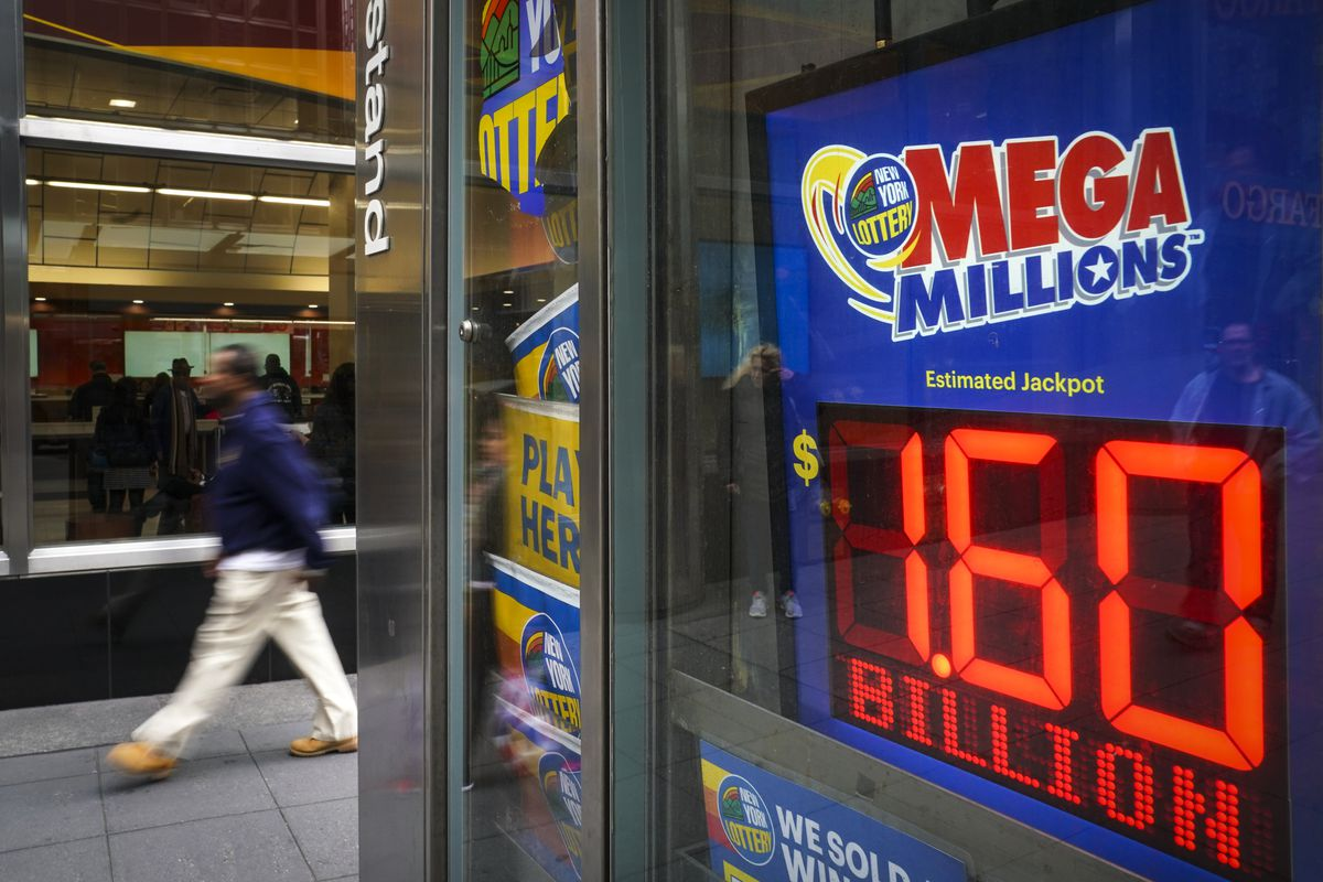 A man walks past a newsstand with advertisements for the Mega Millions lottery in New York City.