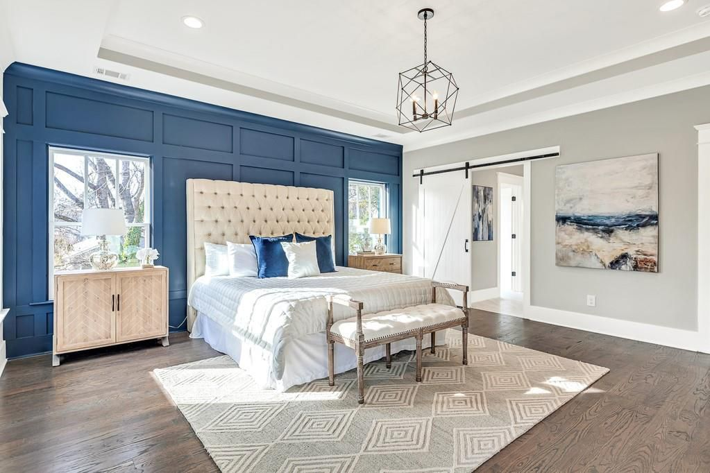 A white and blue bedroom with a huge white bed and white barn door.