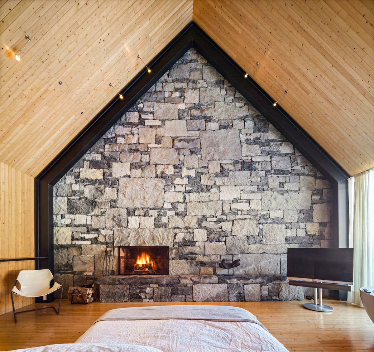 A bedroom has a stone wall with fireplace, black trim, and wooden walls.