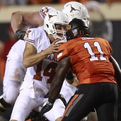 Oklahoma State linebacker Shaun Lewis (11) moves in to sack Texas quarterback David Ash (14) during the second quarter of an NCAA college football game in Stillwater, Okla., Saturday, Sept. 29, 2012.