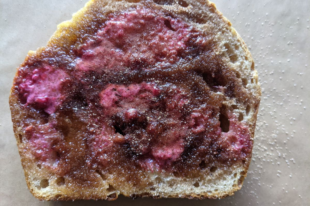 A thick piece of toast is spread with a pinkish fruit butter and cinnamon sugar. It's sitting on a light background.