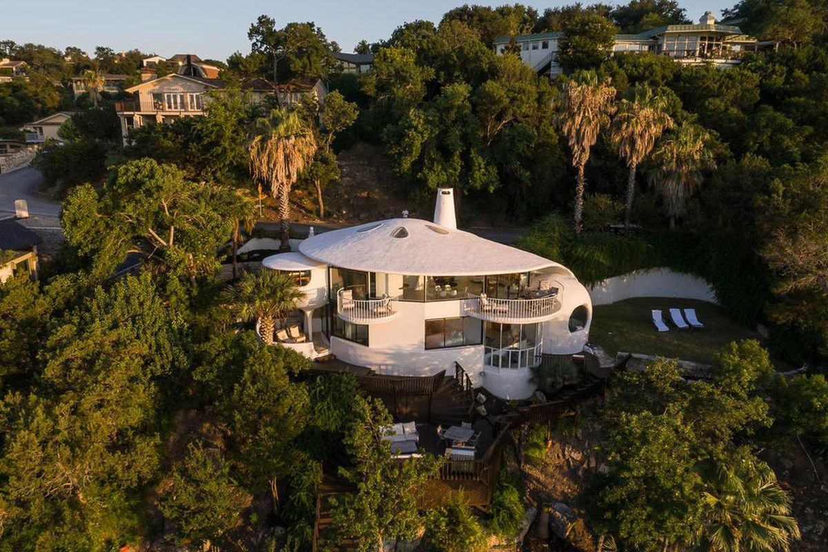 Shot of circular white home topped with roof that looks like a sand dollar. It perches on a wooded bluff.