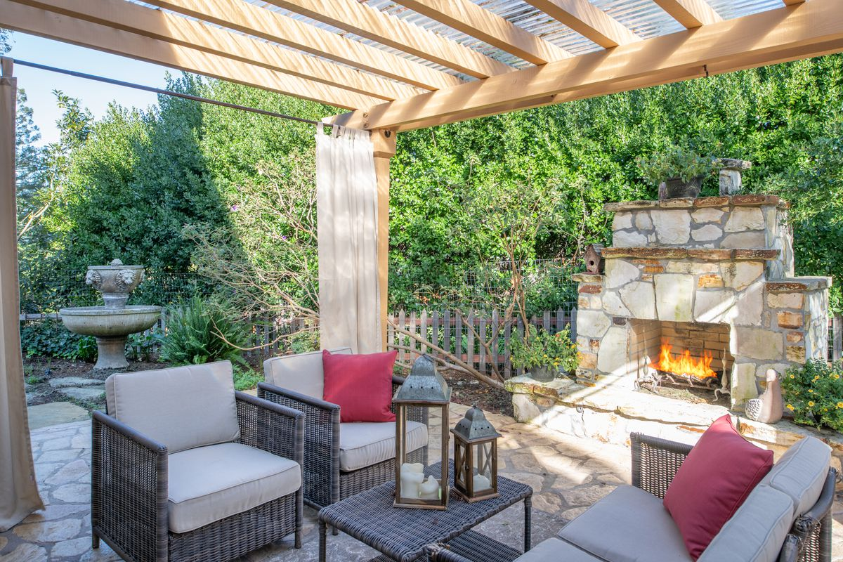 An outdoor living room features a couch, two arm chairs, a coffee table, and a stone fireplace—all sitting below a pergola.