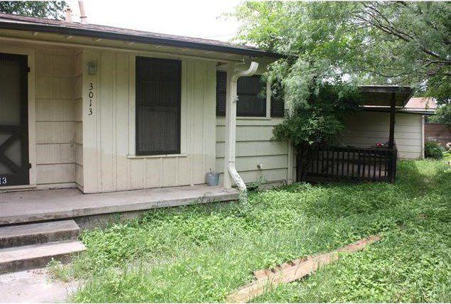 Small, white wood/shingled house with black trim, slightly overgrown yard, possibly a teardown