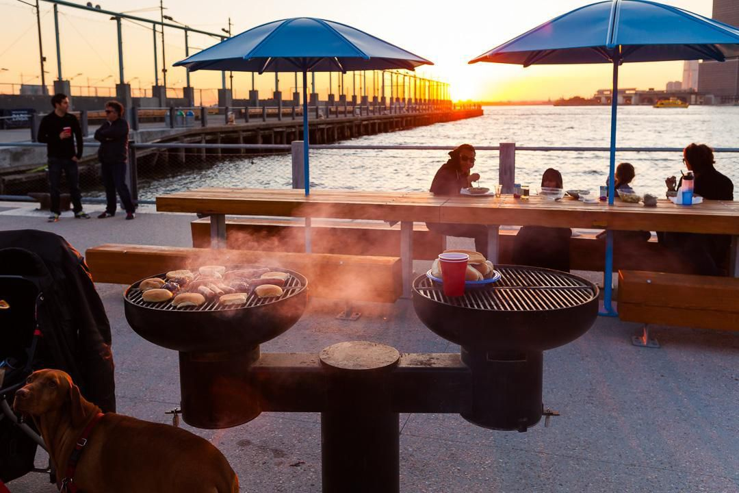 A picnic area with a barbecue grill which has food cooking on it. There are people eating at tables next to a body of water. There is a sunset.