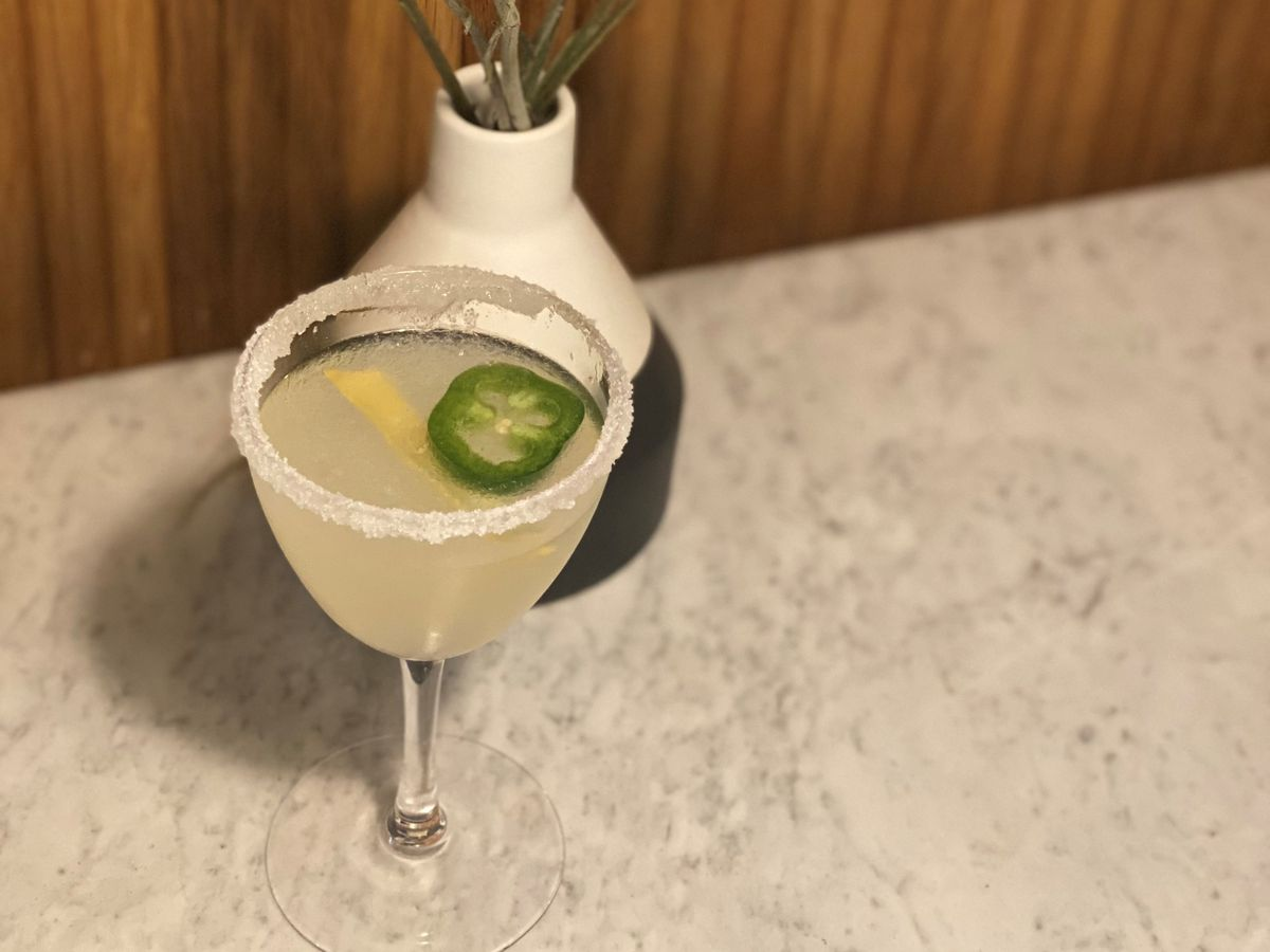 A light yellow cocktail sits in a small wine glass topped with lemon peel and a slice of jalapeno with a sugar rim.