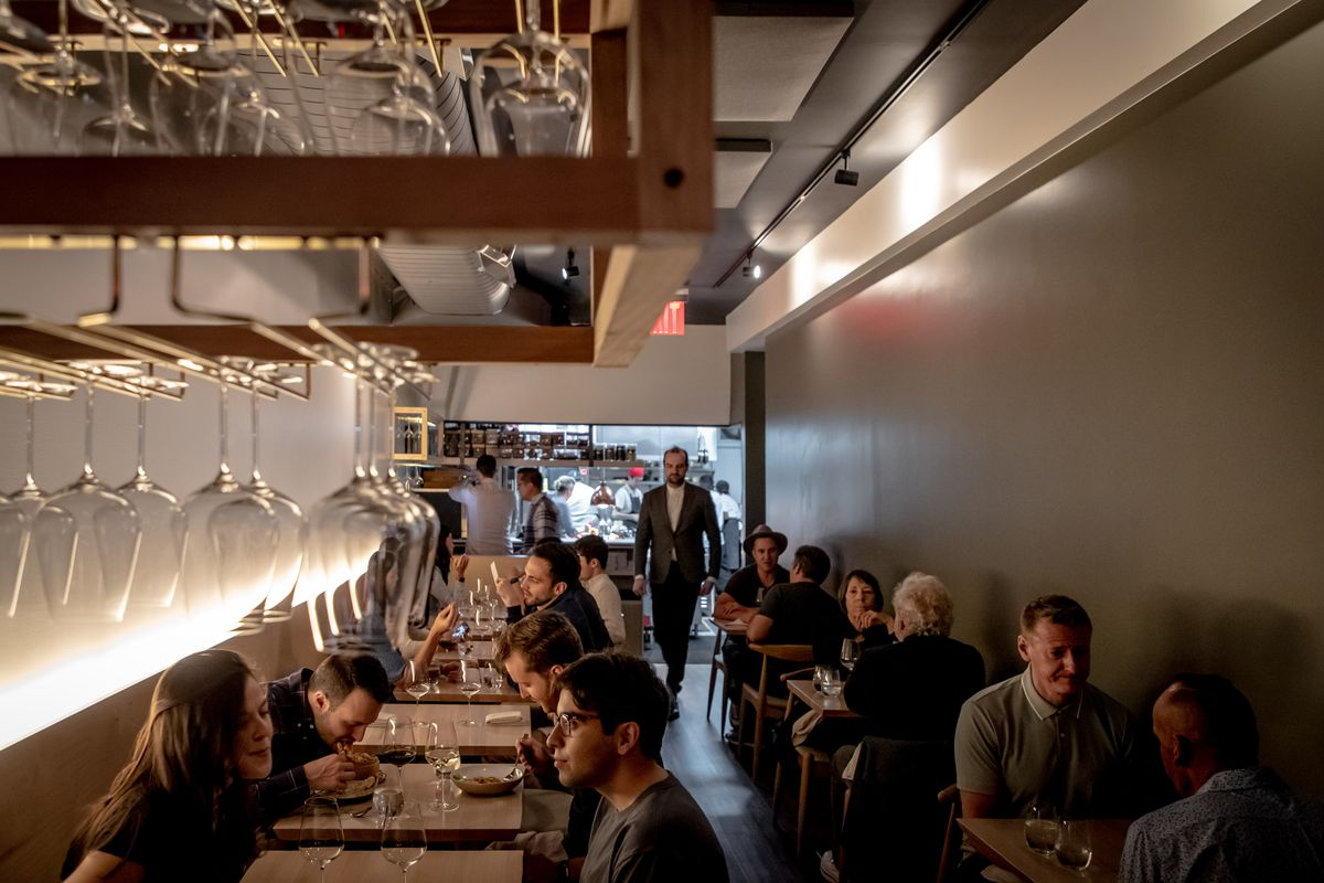 The sommelier walks away from the open kitchen at the back of Red Paper Clip's narrow dining room
