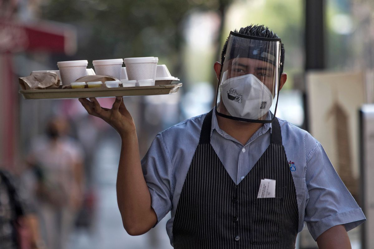 A waiter wearing a mask and face shield carries a tray of plastic food containers