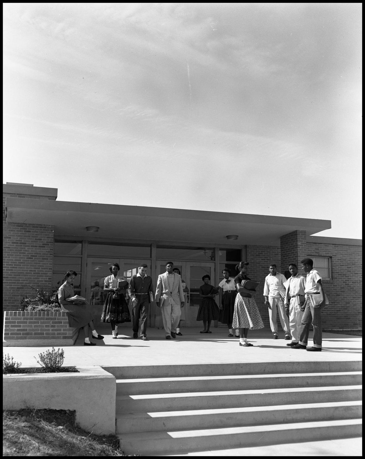 Black and white photo of students hanging out in front of modern-style school building