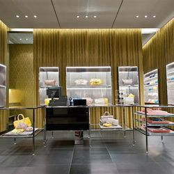 Inside, gold damask curtains surround steel display tables. On the walls, glass display cabinets have mirrored-honeycomb backings.