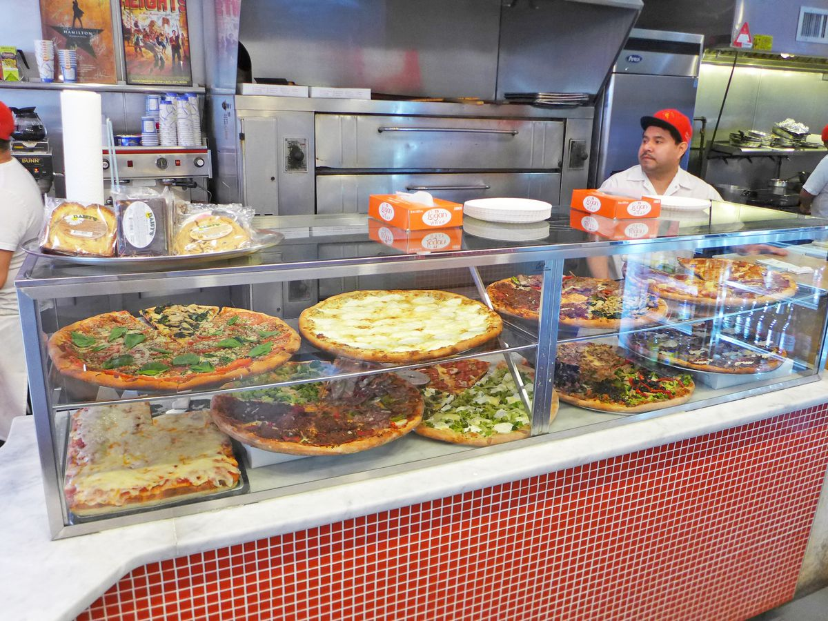 A typical pizzeria counter with pies on display under glass, with three red capped employees behind the counter.
