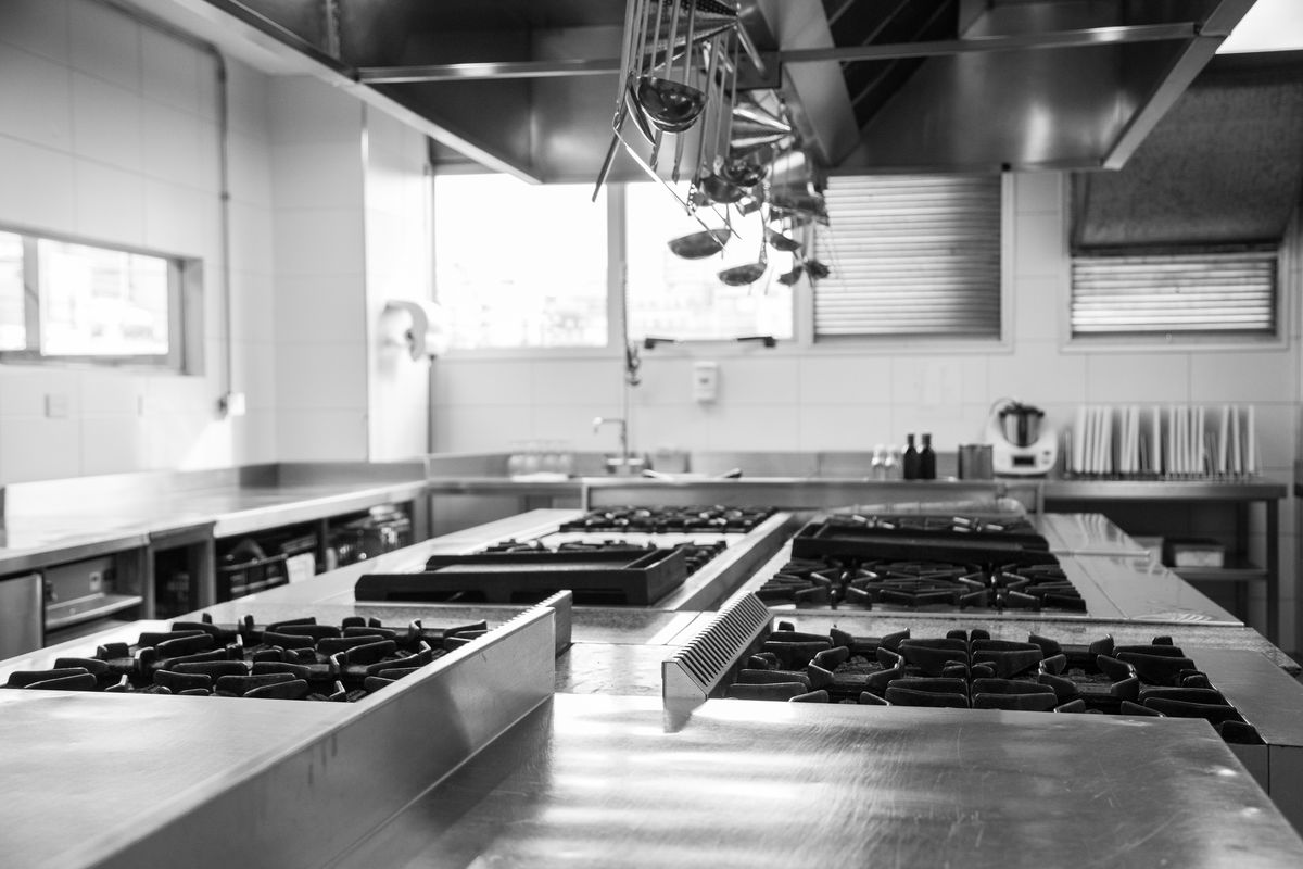 A black and white photo of a large, empty commercial kitchen with stovetops and long stretches of counter space.