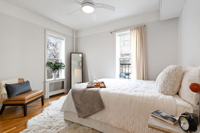 A bedroom with a medium-sized bed, hardwood floors, two windows, and light grey walls.