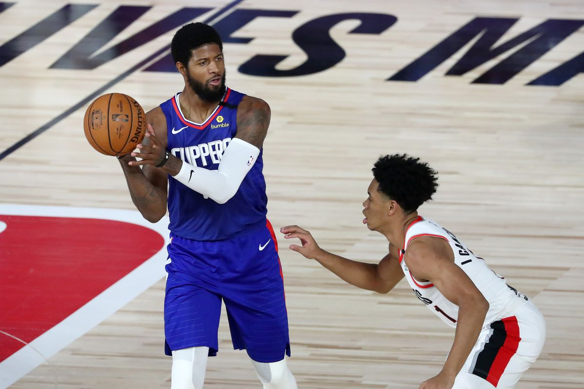 LA Clippers guard Paul George looks to pass as Portland Trail Blazers guard Anfernee Simons defends during the first half against the LA Clippers in an NBA basketball game at The Field House.