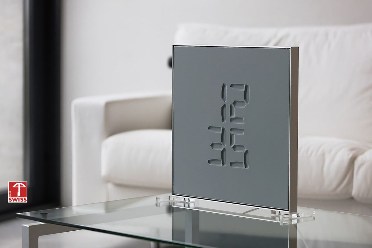 A small square, grey frame standing on a table with the time 'etched' into the surface in digital numbers.