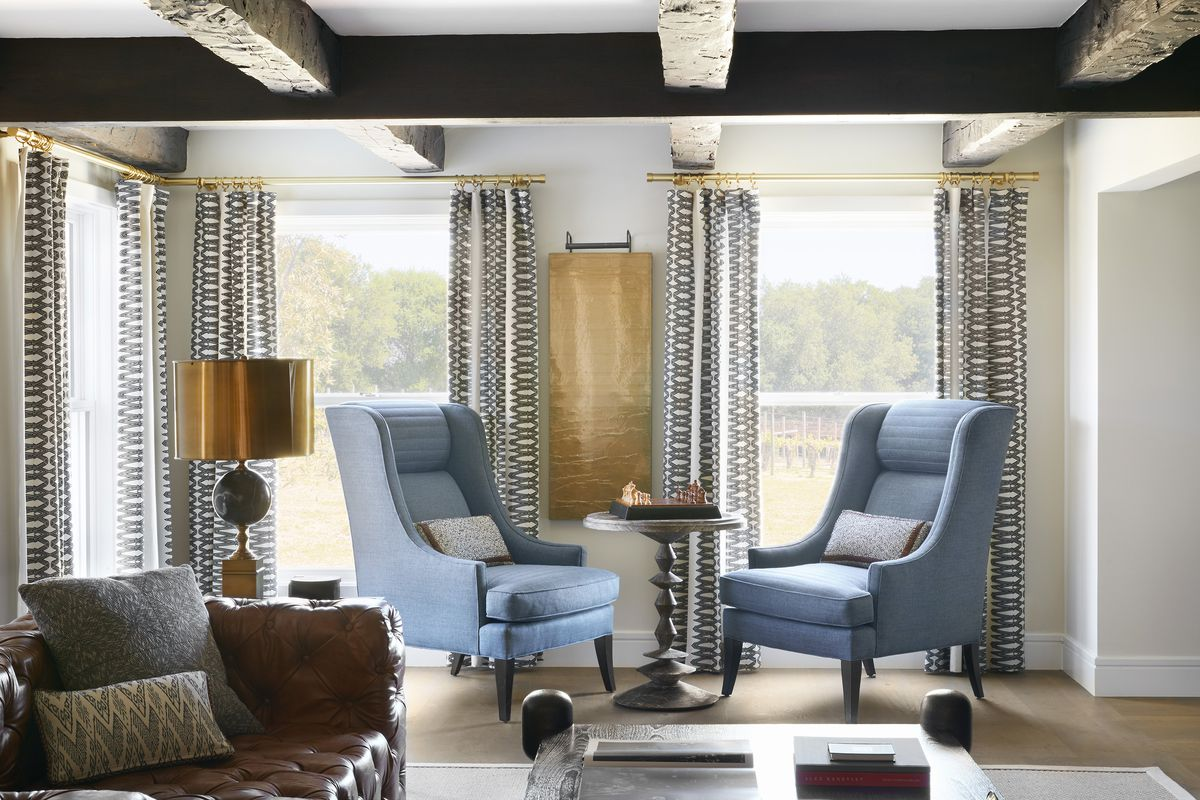 Two blue armchairs flank a small round table with a chess set on top of it.