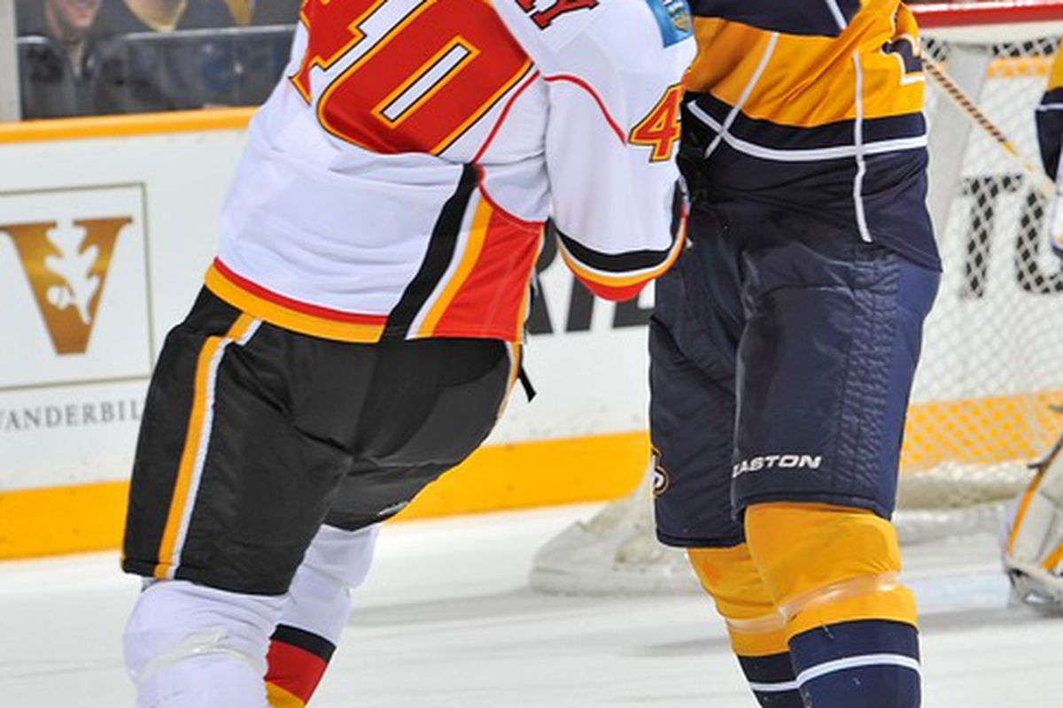 NASHVILLE, TN - DECEMBER 13:  Ryan Suter #20 of the Nashville Predators checks Alex Tanguay #40 of the Calgary Flames at the Bridgestone Arena on December 13, 2011 in Nashville, Tennessee.  (Photo by Frederick Breedon/Getty Images)