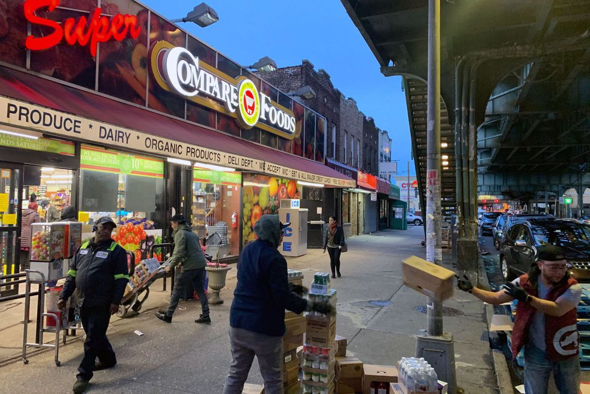 Workers help stock Ozone Park-based Compare Foods.