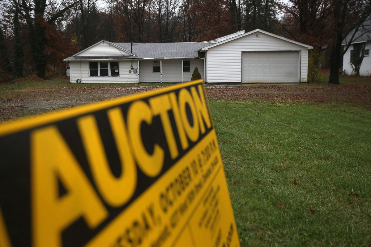 An auction sign in front of a foreclosed house on October 29, 2012 in Warren, Ohio.
