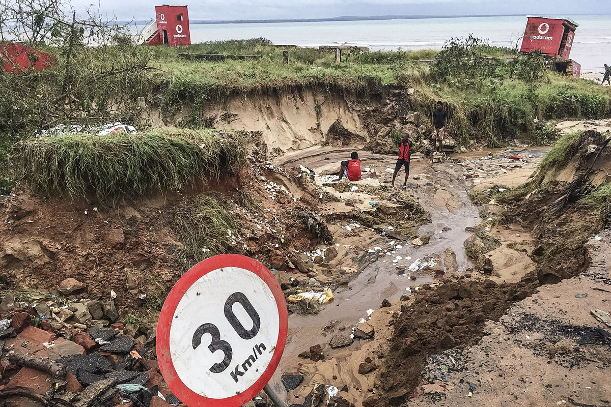 Two residents of Pemba, Mozambique stand in a crater left in a road by Cyclone Kenneth.