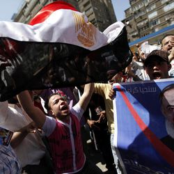 Egyptian supporters of a potential  presidential candidate Hazem Abu Ismail hold posters  and a national flag as they gather outside a courtroom in Cairo, Egypt, Wednesday, April 11, 2012. Abu Ismail is challenging authorities to produce evidence backing their allegations that his mother has a U.S. citizenship, thus disqualifying him from the presidential race.