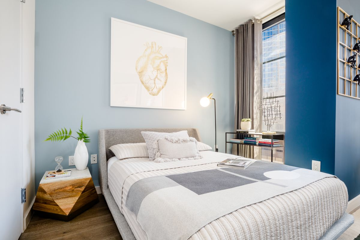 A bedroom with a medium-sized bed, a large window, blue walls, and hardwood floors.