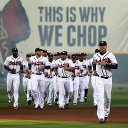 Atlanta Braves players run onto the field  during a ceremony before their home opener against the Milwaukee Brewers in a baseball game in Atlanta, Friday, April 13, 2012.