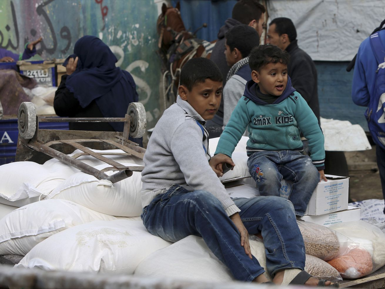 Palestinian refugees sit on sacks of flour that their family received from a UN food distribution center in the Nusseirat refugee camp, central Gaza Strip, Wednesday, January 17, 2018.