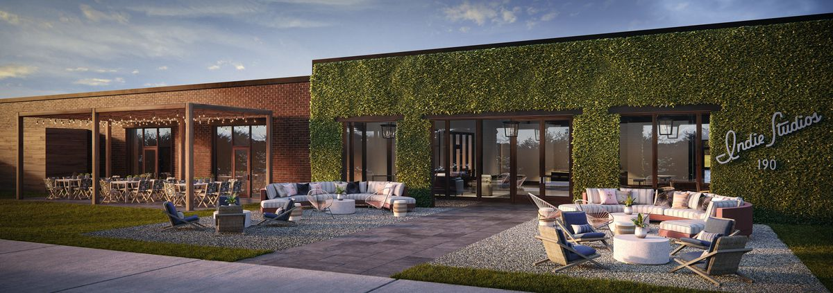 Warehouse with chairs out front and leafy or brick walls.