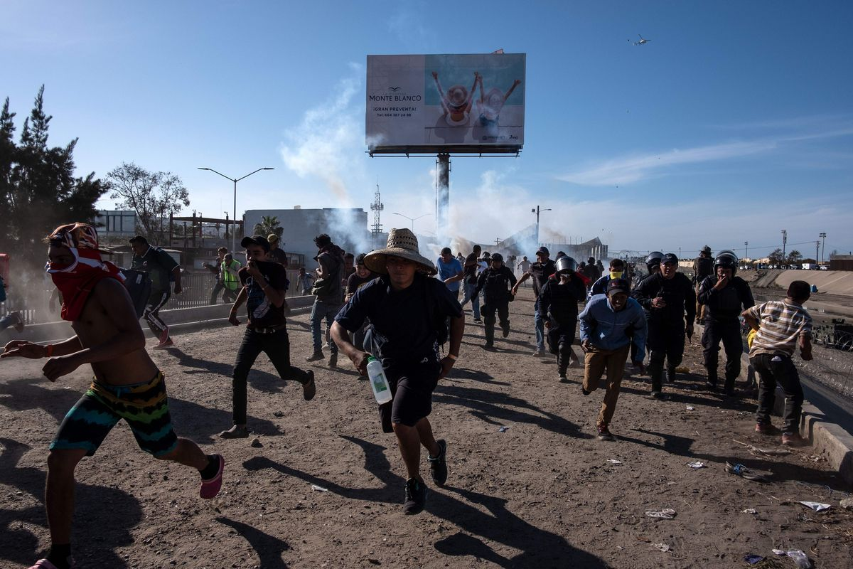 central american migrants run along the tijuana river near a border crossing after border patrol agents used tear gas on november 25 2018