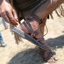 Cooper Sutton, who plays Sam, pulls thistle pieces out of his foot on the set of the Book of Mormon Visual Library at LDS Motion Picture Studios South Campus near Goshen on Friday, July 7, 2017.