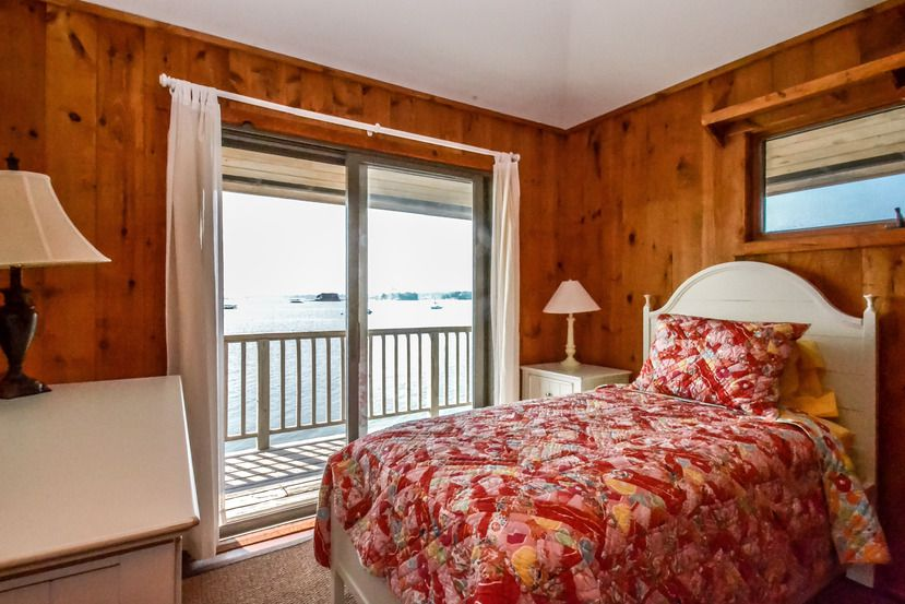 A small bedroom has a red floral quilt on a white bed in a wood paneled room.