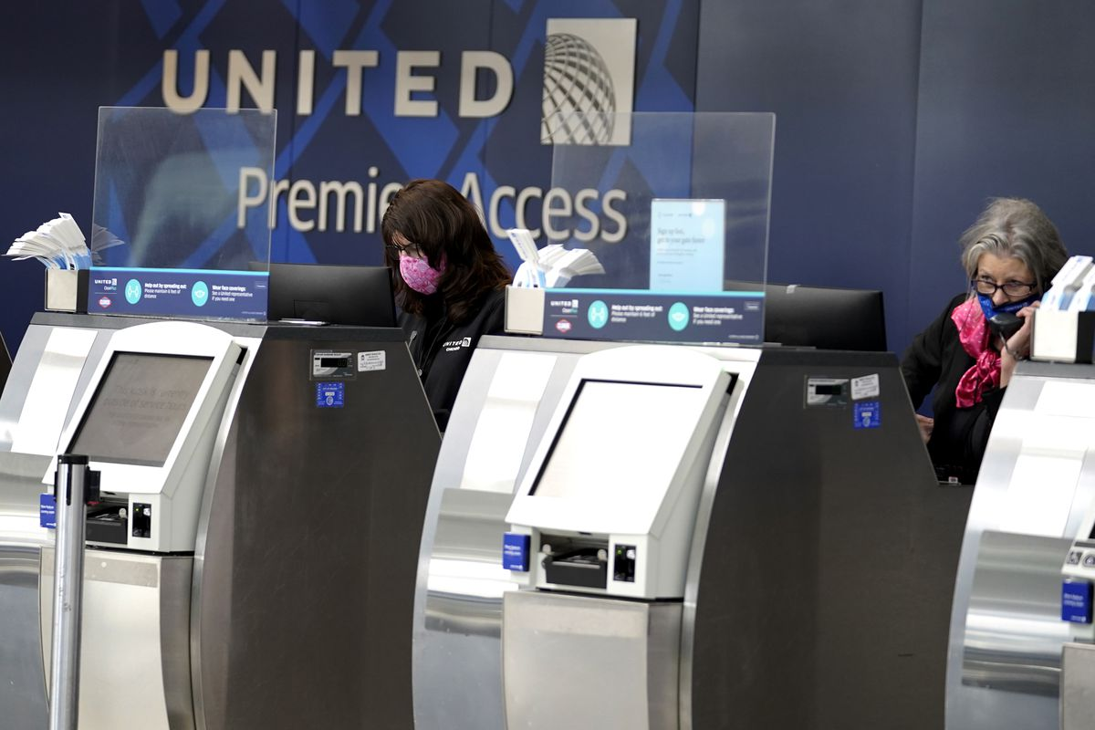 United Airlines employees work at ticket counters in Terminal 1 at O'Hare International Airport in Chicago, on Oct. 14, 2020.