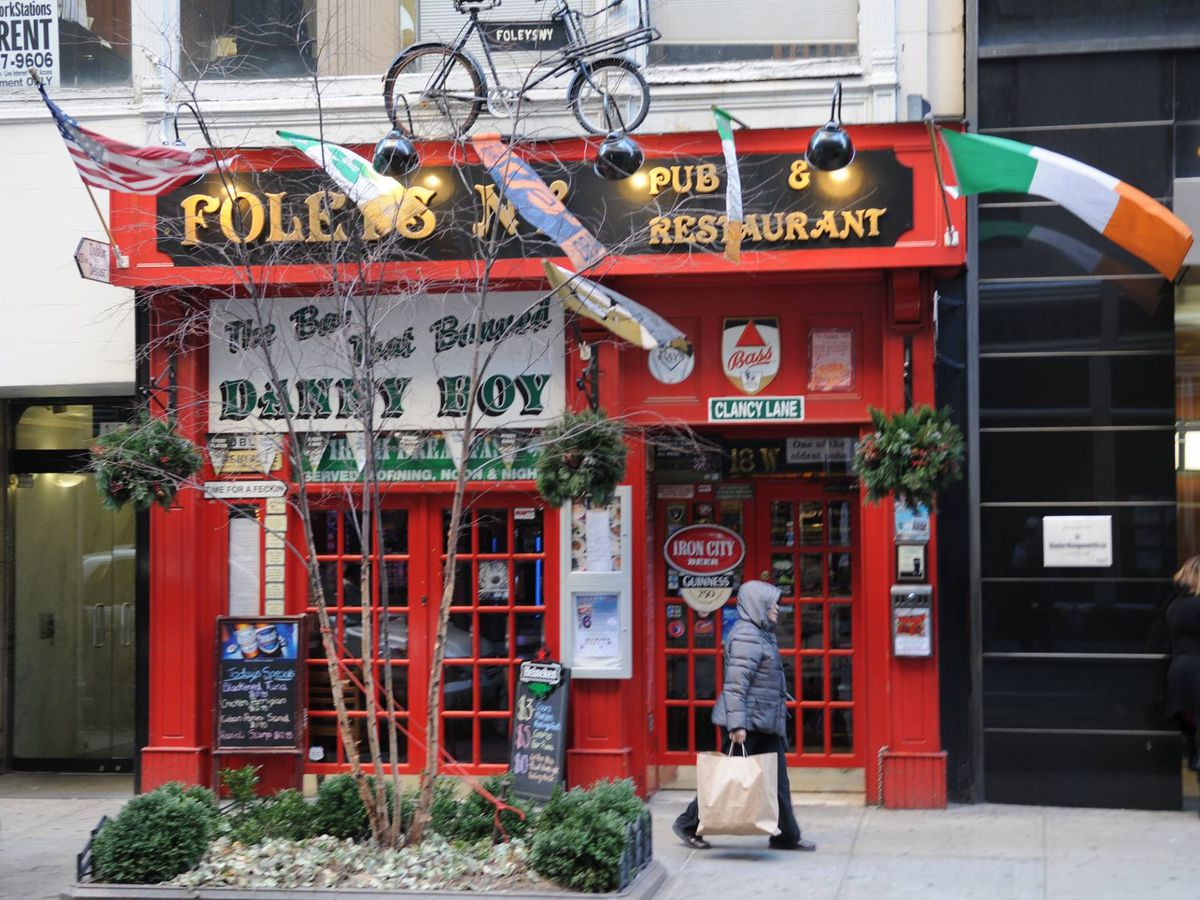 The red exterior of a sports bar called Foley's, with flags hanging off the front