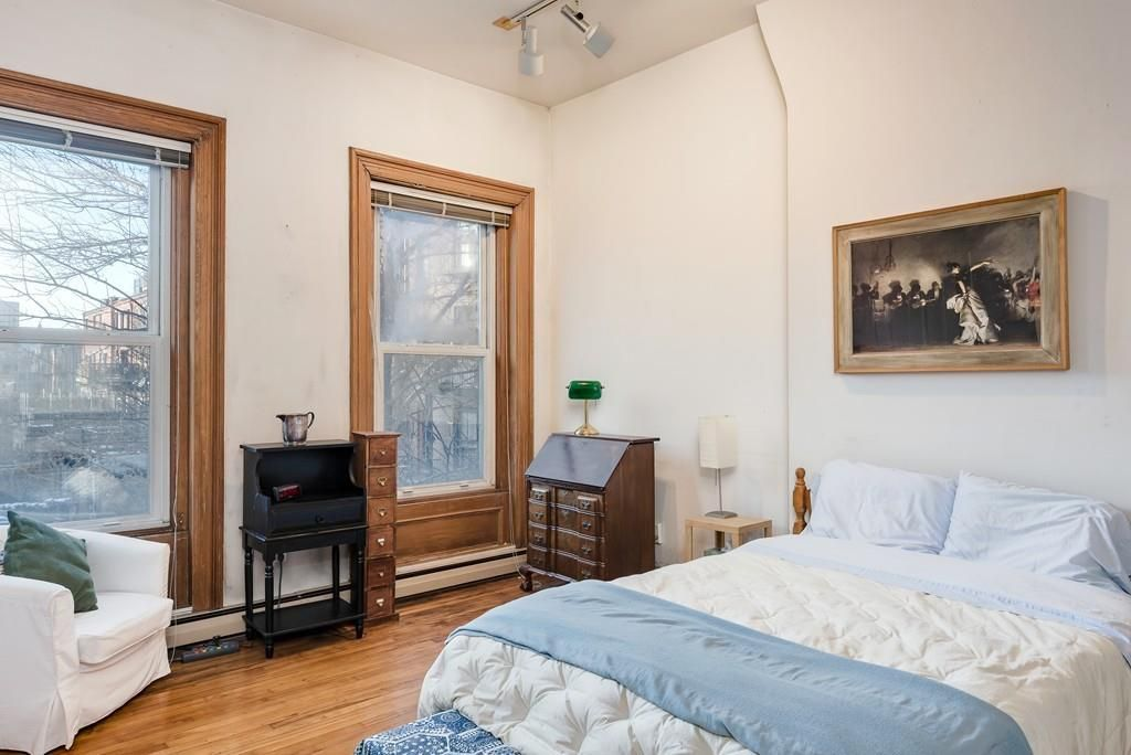 A bedroom with a bed, two nightstands, and two windows.