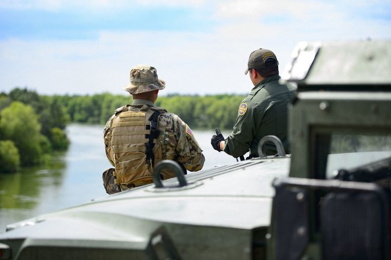 A Texas National Guardsman and a Customs and a Border Protection agent discuss the border security mission on the shores of the Rio Grande River in Starr County, Texas, April 10, 2018.