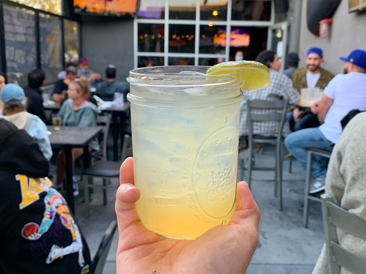 A pale yellow cocktail in a mason jar with ice topped with lemon