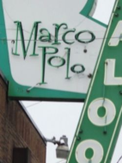 Exterior of Marco Polo, showing a retro green sign for the saloon.