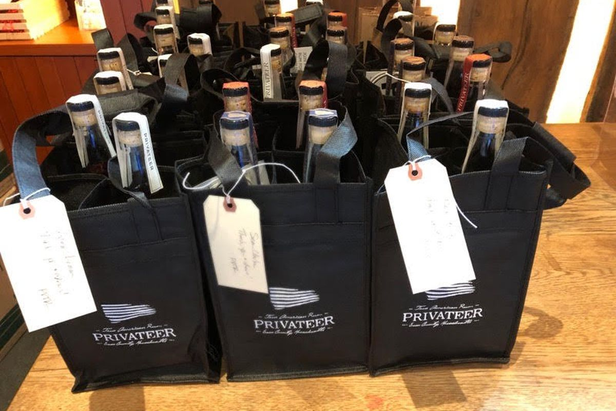 A group of small black tote bags with Privateer Rum branding, each filled with bottles of rum, are lined up on a tabletop