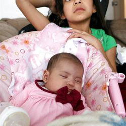 Ariza Carreon, 7, watches over her baby sister Adriana at home in Taylorsville on Saturday, Feb. 9, 2013. Carreron's family was recently evicted, but they managed to land on their feet.