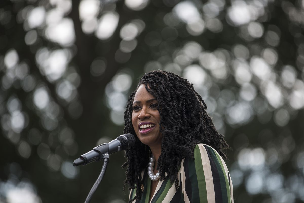 Rep. Ayanna Pressley speaks outdoors into a microphone
