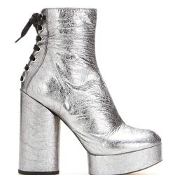 The style recalls David Bowie's Ziggy Stardust, balancing the strong element of a chunky heel and platform front with the delicateness inherent in wearing any high high heel.