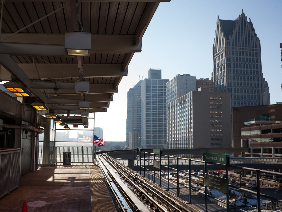 An elevated train platform next to train tracks. In the distance is a city skyline with tall buildings.