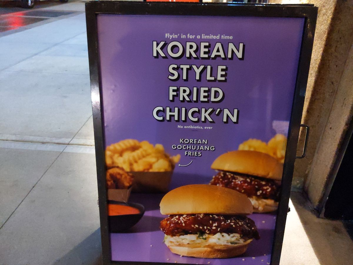 A swinging sign shows a chicken sandwich and some fries, in front of Shake Shack