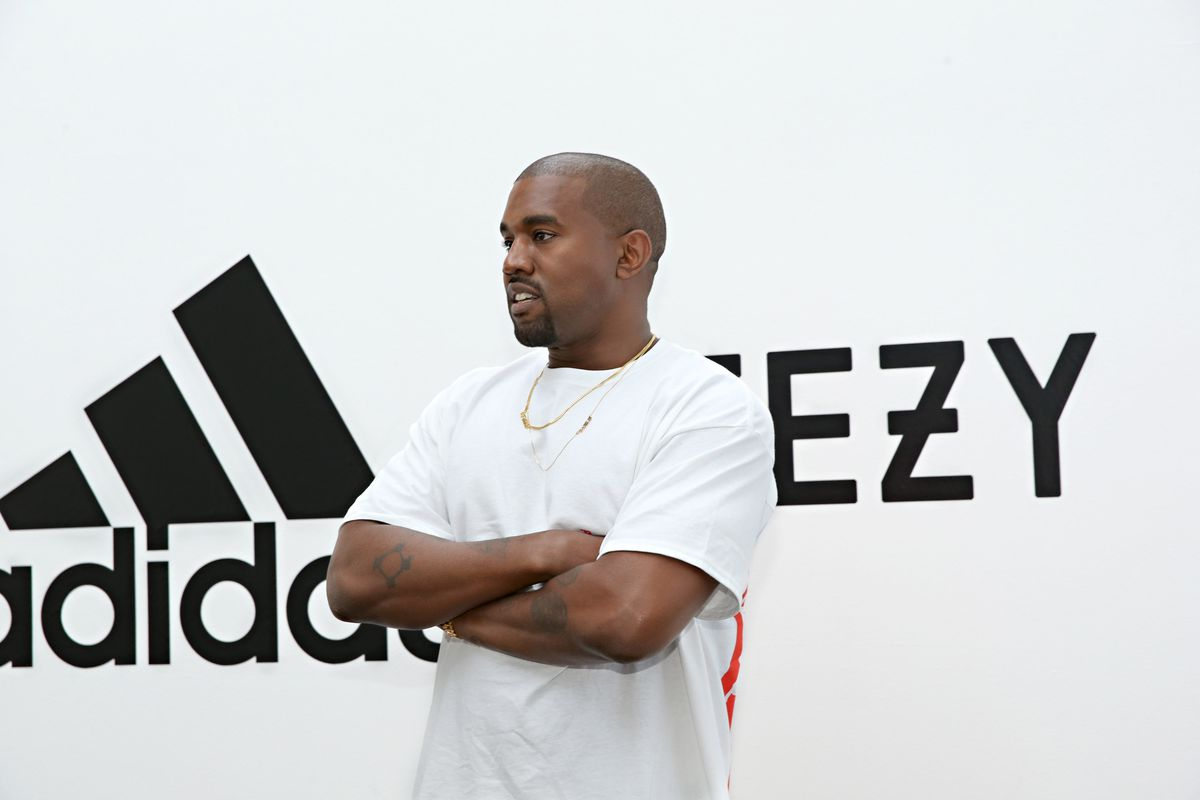 Kanye West wears a white Yeezy shirt at the announcement of his partnership with Adidas.