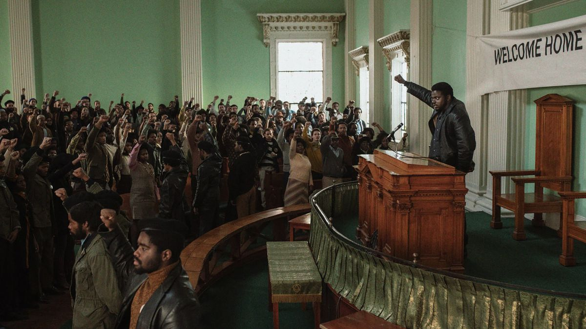 Daniel Kaluuya as Fred Hampton stands behind a lectern, holding his fist up as he leads a packed church hall in a Black Power chant.
